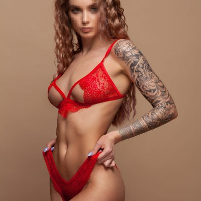 Katie Stripper in red with tattoos